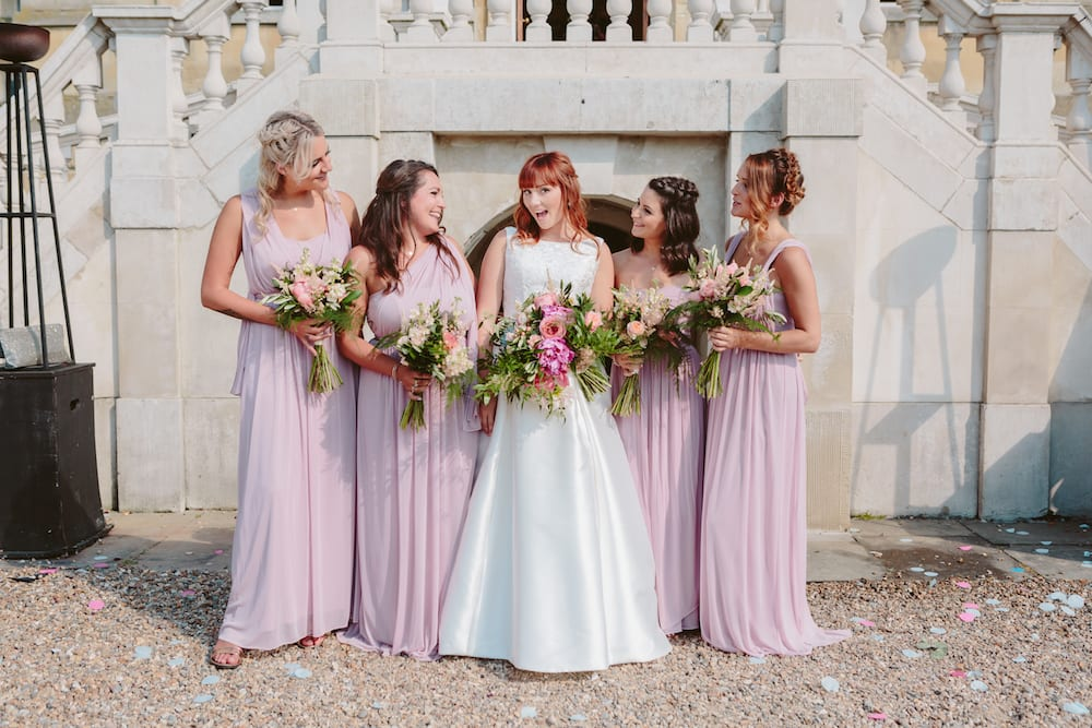 Bridal party with brightly coloured floral bouquets pastel pinks blush